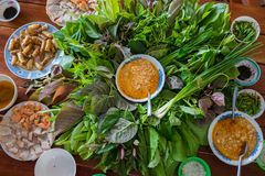 Peculiar herbs salad in Kon Tum, Vietnam. Using the leaves to make a cone-shaped container to put the food in, and use some bacon,. Fried shrimp, sliced pork Stock Photos