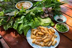Peculiar herbs salad in Kon Tum, Vietnam. Using the leaves to make a cone-shaped container to put the food in, and use some bacon,. Fried shrimp, sliced pork Royalty Free Stock Photo