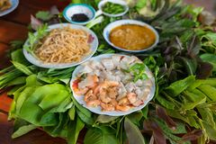 Peculiar herbs salad in Kon Tum, Vietnam. Using the leaves to make a cone-shaped container to put the food in, and use some bacon,. Fried shrimp, sliced pork Stock Photography