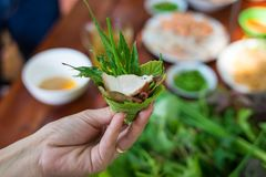 Peculiar herbs salad in Kon Tum, Vietnam. Using the leaves to make a cone-shaped container to put the food in, and use some bacon,. Fried shrimp, sliced pork Royalty Free Stock Image