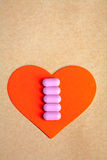 Ped paper heart shape over craft paper with row of small pink pill on. Heart health. Stock Image