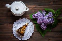 Pedaço de bolo, bule e lilás em um fundo de madeira Foto de Stock