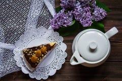 Pedaço de bolo, bule e lilás em um fundo de madeira Imagens de Stock Royalty Free