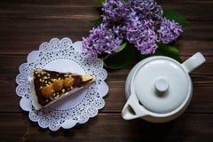 Pedaço de bolo, bule e lilás em um fundo de madeira Imagem de Stock