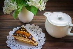 Pedaço de bolo, bule e lilás em um fundo de madeira Fotografia de Stock