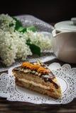 Pedaço de bolo, bule e lilás em um fundo de madeira Fotos de Stock