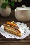Pedaço de bolo, bule e lilás em um fundo de madeira Imagem de Stock Royalty Free