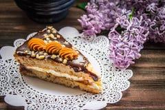 Pedaço de bolo e um lilás no fundo de madeira marrom Fotos de Stock