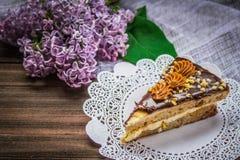 Pedaço de bolo e um lilás no fundo de madeira marrom Foto de Stock