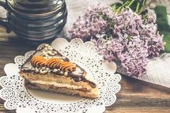 Pedaço de bolo e um lilás no fundo de madeira marrom Imagens de Stock