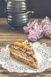 Pedaço de bolo e um lilás no fundo de madeira marrom Imagem de Stock Royalty Free
