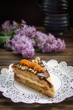 Pedaço de bolo e um lilás no fundo de madeira marrom Fotos de Stock Royalty Free