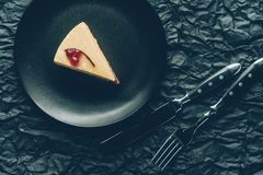 Pedaço de bolo na placa e na cutelaria no tabletop escuro Imagens de Stock Royalty Free