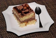 Pedaço de bolo quadrado com chocolate e amêndoa na placa branca fotos de stock royalty free