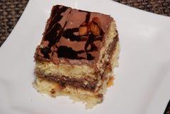Pedaço de bolo quadrado com chocolate e amêndoa na placa branca fotos de stock