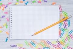 Pedaço de papel vazio em uma gaiola, na tabela com um lápis cercado por grampos multi-coloridos foto de stock