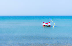 Pedalò rosso e bianco su un mare blu calmo, vicino alle boe gialle Fotografia Stock Libera da Diritti
