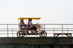 Pedal On The Boardwalk 2. Two couples riding a pedal vehicle on a boardwalk royalty free stock photos