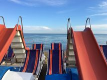 Pedal boat Pedal with slides and deck chairs, in calm blue sea background with white clouds on the horizon royalty free stock image