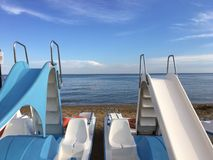 Pedal boat Pedal with slides and deck chairs, in calm blue sea background with white clouds on the horizon royalty free stock photo