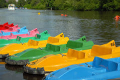 Pedal Boats. Of various colours all lined up at the river bank waiting to be used with river scene in the background Stock Photos