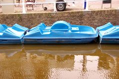 Pedal boats. Blue pedal boats in a canal of an old city Royalty Free Stock Photo