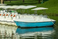 Pedal boats floating in the water at the park. stock photos