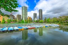 Ueno Park Tokyo. Pedal boats and Tokyo skyscrapers reflecting on Shinobazu Pond in Ueno Park, a public park next to Ueno Station in central Tokyo. Ueno Park is Royalty Free Stock Photos