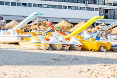 Pedal catamarans for active recreation on sand beach. In sunlight Royalty Free Stock Photography