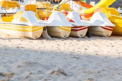 Pedal catamarans for active recreation on sand beach. In sunlight Royalty Free Stock Photo