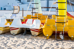 Pedal catamarans for active recreation on sand beach. In sunlight Royalty Free Stock Image