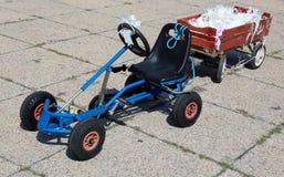 Pedalen går-kart med en vagn med flingor som klibbas till bruden och groen Fotografering för Bildbyråer
