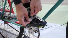 Pedali dei legami del ciclista con le clip del dito del piede su una bicicletta d'annata della pista sul portone di riciclaggio d video d archivio