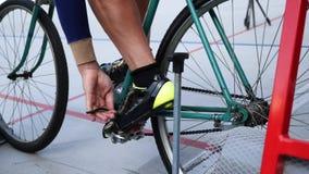 Pedali dei legami del ciclista con le clip del dito del piede su una bicicletta d'annata della pista sul portone di riciclaggio d archivi video