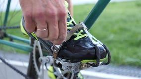 Pedali dei legami del ciclista con le clip del dito del piede su una bicicletta d'annata della pista sul velodromo stock footage