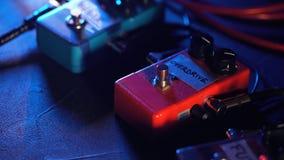 Pedali ed interruttore a pedale della chitarra dentro sala di registrazione Chiuda su dei pedali della chitarra e del piede del ` stock footage