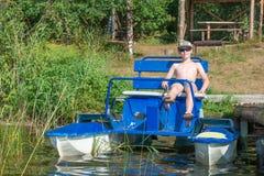 pedalo小船的微笑的男孩 免版税库存图片