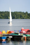 Pedalos at jetty, sailboat on lake Stock Image