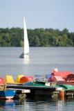 Pedalos at jetty, sailboat on lake Stock Image