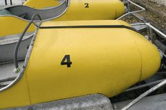 Pedalos. Old yellow pedalos moored on lakeshore royalty free stock photos