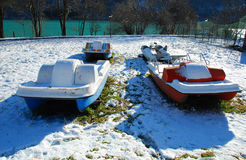 Pedalos in Snow. Plastic pedalos lie disused in the mid-winter besides an alpine lake royalty free stock photo