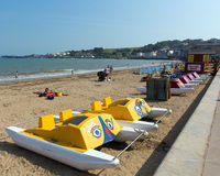 Pedalos Swanage beach Dorset England UK with waves on the seashore. Sunny weather brought families and visitors to Swanage on the Dorset coast to enjoy the royalty free stock photo