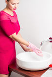 Pedantic woman cleaning sink Stock Photography