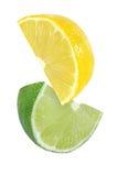 Pedazo colgando, el caer y el volar de frutas del limón y de la cal aisladas en blanco con la trayectoria de recortes Foto de archivo