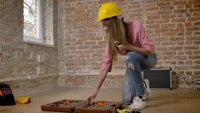 Pedazo confiado joven de herramienta, concepto constructivo del cambio del constructor de la muchacha almacen de video