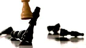 Pedazo de ajedrez blanco que golpea sobre muchos pedazos negros metrajes