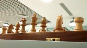 Pedazo de ajedrez en tablero de ajedrez con el fondo de la decoración del techo fotos de archivo