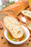 Pedazo de baguette en un aceite, especias y ajo de oliva fragante Fotografía de archivo libre de regalías