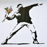 Pedazo de Banksy de un alborotador que lanza un ramo de la flor Imagen de archivo libre de regalías