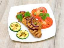 Pedazo de carne asada con las verduras en una placa blanca Imagen de archivo libre de regalías